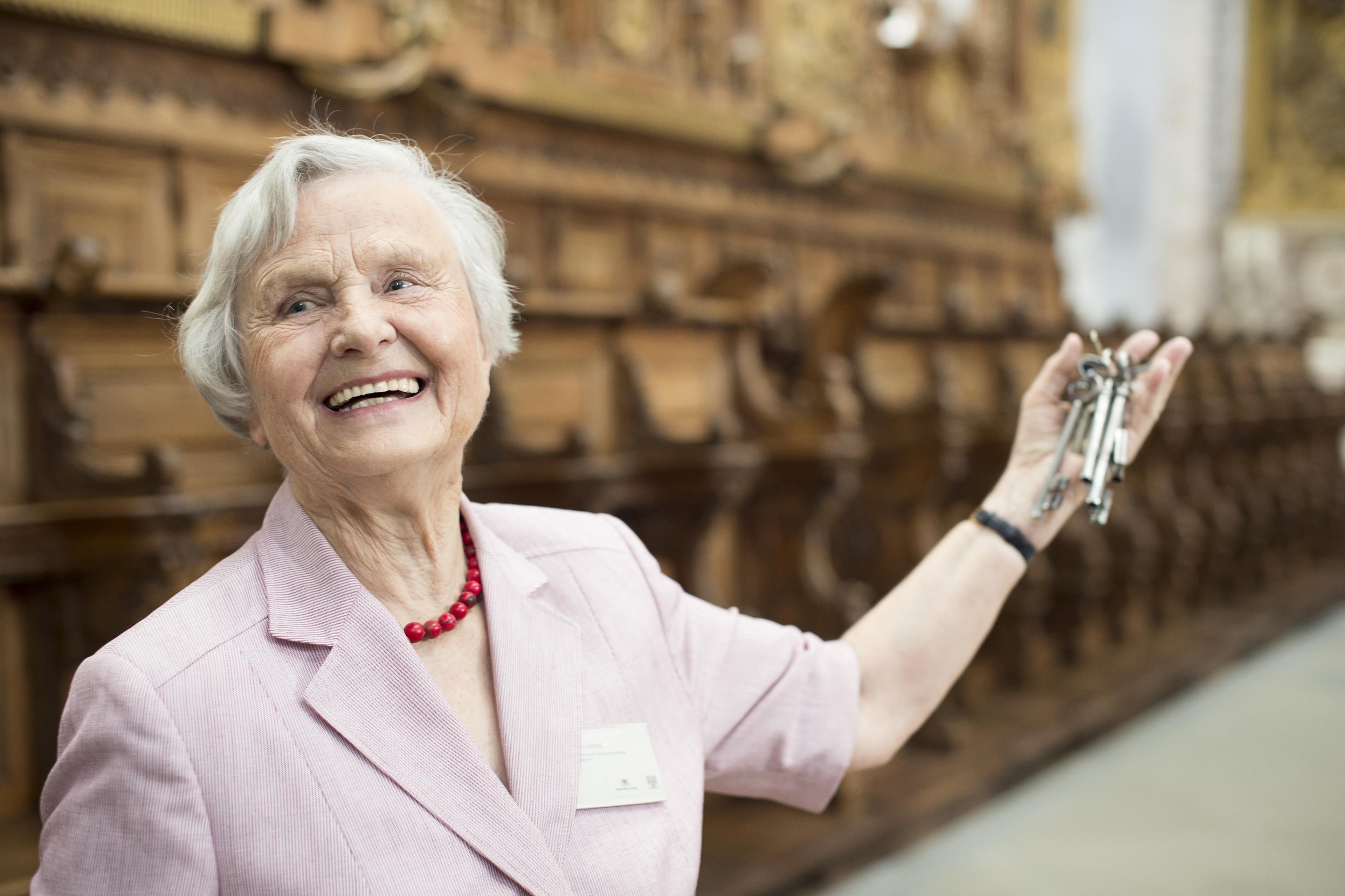 Ältere Dame zeigt Raum,; Foto: Staatliche Schlösser und Gärten Baden-Württemberg, Niels Schubert