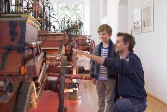 Erwachsener zeigt Kind ein Ausstellungsstück des Feuerwehrmuseums